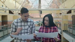 Woman in a pink plaid shirt gives a man the sheets from the stack. stock footage