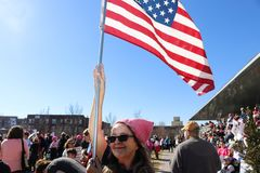 Woman with pink hat hold American flag high over crowd at Womens March Tulsa Oklahoma 1-20-2018 stock photography