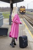 The woman in a pink raincoat at the railway station Royalty Free Stock Images