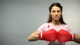 Woman with pink ribbon in boxing gloves, fighting against breast cancer concept royalty free stock photo