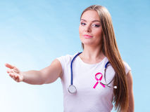 Woman pink ribbon on chest making welcome gesture. Healthcare, medicine and breast cancer awareness concept. Doctor with pink ribbon aids symbol, inviting making Stock Photography