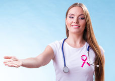 Woman pink ribbon on chest making welcome gesture. Healthcare, medicine and breast cancer awareness concept. Doctor with pink ribbon aids symbol, inviting making Stock Photo