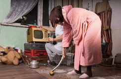 Woman in Pink Robe Cleaning a Messy Room Royalty Free Stock Photography