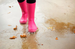 Woman with pink rubber boots walking through puddle in autumn Royalty Free Stock Photo