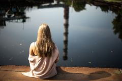 Woman in Pink Shirt Fronting Body of Water Stock Images