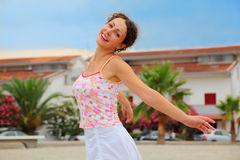 Woman in pink shirt spinning on beach. Beautiful young woman in pink shirt spinning on beach and smiling Stock Images