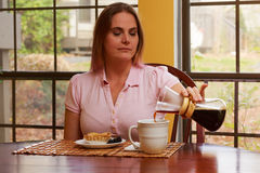 Woman in pink shirt at table Royalty Free Stock Photography