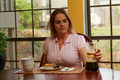 Woman in pink shirt at table Stock Photography