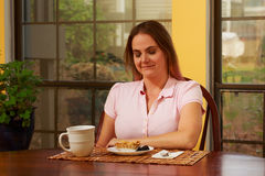 Woman in pink shirt at table Royalty Free Stock Images