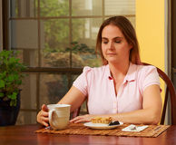 Woman in pink shirt at table Royalty Free Stock Image