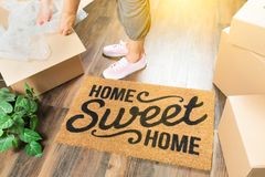 Woman in Pink Shoes and Sweats Unpacking Near Home Sweet Home. Wman in Pink Shoes and Sweats Unpacking Near Home Sweet Home Welcome Mat, Moving Boxes and Plant Royalty Free Stock Image