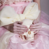Woman in pink silk dress holds a skull stock photo