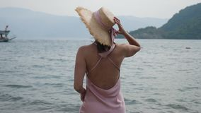 Woman in pink silk dress and straw hat stand on the beach. In Turkey stock footage