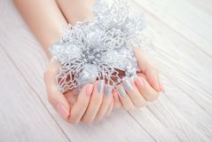 Woman with pink and silver manicure holds silver poinsettia. On wooden background stock photo