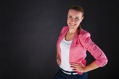Woman in pink siute over dark background smiling Stock Photo