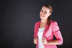 Woman in pink siute over dark background smiling Royalty Free Stock Photography