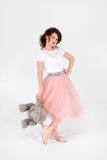woman in pink skirt holding big soft teddy bear on white background Royalty Free Stock Image