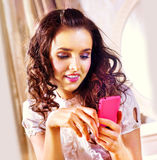 Woman with pink smartphone Royalty Free Stock Photography