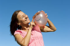 Woman with pink smiley balloon III. Portrait of a happy looking mature woman in her fifties, wearing a pink shirt and sunglasses, holding a colour matching Stock Photo