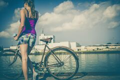 Woman in Pink Spaghetti Strap Dress Holding a Brown Road Bicycle during Day Time Royalty Free Stock Photo