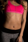 Woman in pink sports bra on black body arm down Stock Image