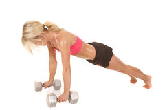 Woman pink sports bra push up arms straight. A woman working out by doing push ups on her weights Stock Photo