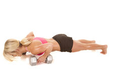 Woman pink sports bra push up. A woman working out by doing push ups on her weights Stock Photography