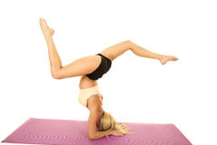 Woman pink sports bra side on head legs up out. A woman in her fitness clothing doing a head stand showing off her strength and balance Royalty Free Stock Photography