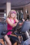 Woman in pink sportswear doing exercise Stock Photos