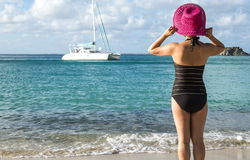 Woman with Pink Straw Hat Looking at a Catamaran Stock Images
