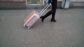 Woman with pink suitcase. Walking stock video