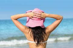 Woman with pink sun hat in summer towards the sea Royalty Free Stock Photos