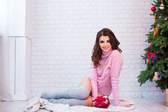 Woman in pink sweater near a Christmas tree. Royalty Free Stock Photography