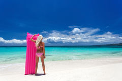 Woman with pink swimming mattress on tropical beach, Philippines Royalty Free Stock Photography