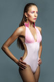 Woman in pink swimsuit on gray background Stock Photography