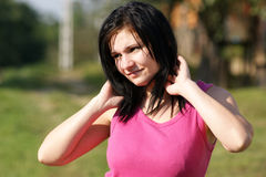 woman with pink T-shirt looks into the sun royalty free stock photography