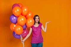 Woman in pink t-shirt posing with bright colorful air balloons