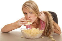 Woman pink tank top chips lean over eat Stock Image
