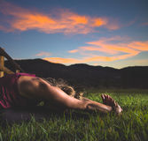 Woman in Pink Tank Top Doing Yoga on Green Grass during Dawn Stock Photos