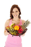 Woman pink tank top fruit smile. A woman standing and holding a bowl full of fruit with a smile on her face Stock Photo