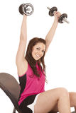 Woman pink tank top weights up. A woman in a pink tank top is holding weights above her head Stock Images
