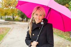 Woman with pink umbrella enjoying autumn stock photos