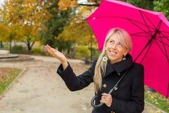 Woman with pink umbrella enjoying rainy autumn weather royalty free stock photos