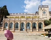 Woman with Pink Umbrella in front of Stone Loggia in Hvar, Croatia stock images
