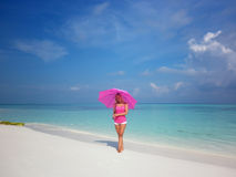 Woman with pink umbrella. Young woman with pink umbrella at tropical white sandy beach Royalty Free Stock Photography