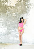 Woman in pink underwear stand against wall Stock Photo