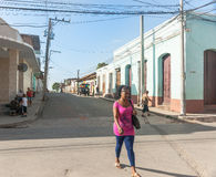 Woman in pink walks along street. Trinidad, Cuba - July 2, 2012: Woman in pink top stands out as she walks along street lined by colonial style in Cuban town Royalty Free Stock Image
