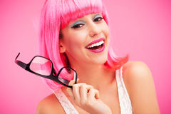 Woman with pink wig and glasses. Woman wearing wig over pink background Royalty Free Stock Photo