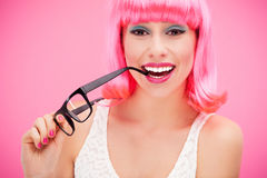 Woman with pink wig and glasses. Woman wearing wig over pink background Royalty Free Stock Image