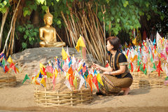 Woman pinned traditional flags. On sand pagoda at temple in Chian royalty free stock images